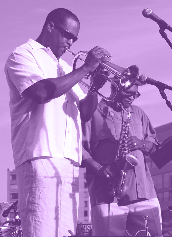 Jazz in June concert performers play trumpet and saxophone on stage