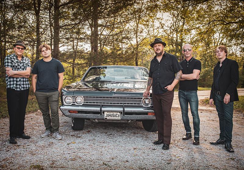 Josh Hoyer, Blake DeForest, Mike Keeling, Benjamin Kushner, Harrison ElDorado stand in front of black vintage convertible on forest road.