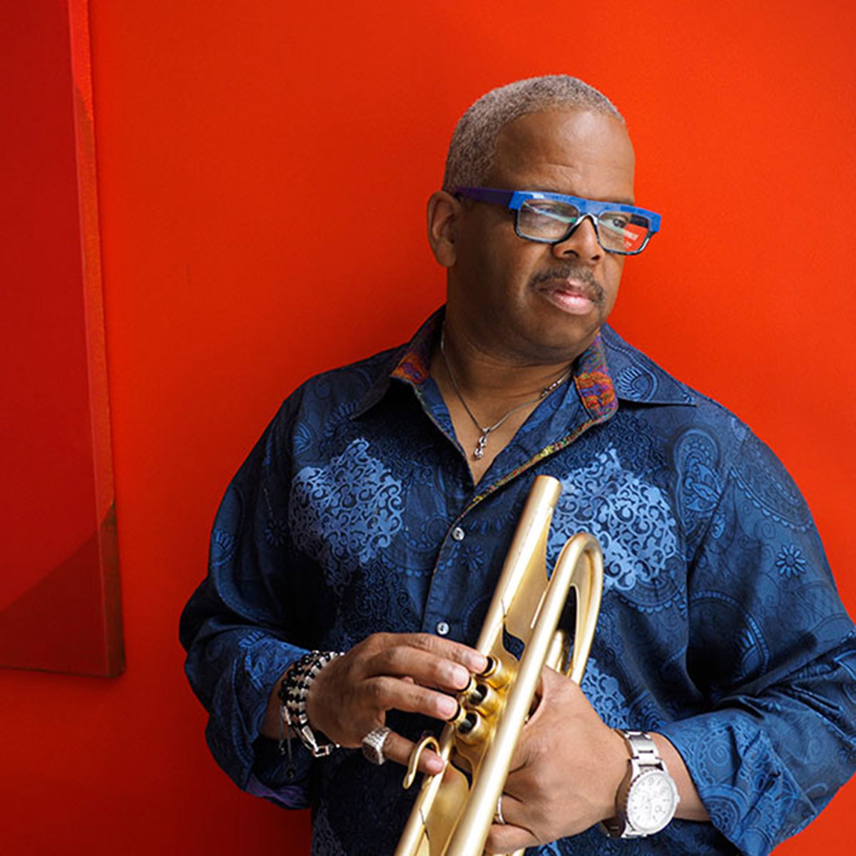 Terence Blanchard holding trumpet in front of orange wall.